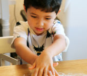 Child kneading pasta dough.